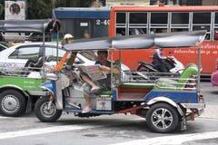 БАНГКОК, ТАИЛАНД 25-ОЕ АПРЕЛЯ: Водитель tuk tuk ждет плату за проезд дальше Стоковые Изображения