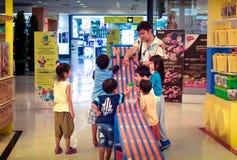 БАНГКОК, ТАИЛАНД - 15-ОЕ АПРЕЛЯ: Неопознанный человек сидит с детьми и r стоковая фотография rf