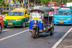 БАНГКОК, ТАИЛАНД 12-ОЕ ДЕКАБРЯ: Tuk Tuk бежит и пассажир поиска Стоковое Изображение