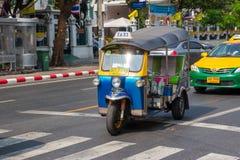 БАНГКОК, ТАИЛАНД 12-ОЕ ДЕКАБРЯ: Tuk Tuk бежит и пассажир поиска Стоковое фото RF