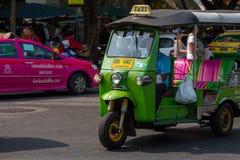 БАНГКОК, ТАИЛАНД 12-ОЕ ДЕКАБРЯ: Tuk Tuk бежит и пассажир поиска Стоковые Фотографии RF