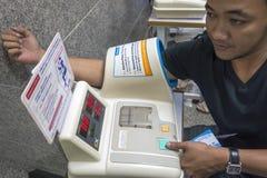 БАНГКОК, ТАИЛАНД - 10-ое марта: Таиланд, тайские люди используя sphygmomano Стоковые Фото