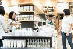 Бангкок, Таиланд - 29-ое июля 2017: Много женщин стоят покупая забота кожи косметик на магазине косметик Они выбирают необходимое Стоковое Изображение RF