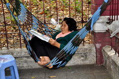 Бангкок, Таиланд: Чтение женщины в гамаке Стоковое Изображение