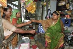 Бангладешский женский бакалейщик продает рис и масло Стоковая Фотография
