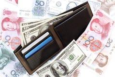 Банкнота доллара в бумажнике на предпосылке банкноты юаней Стоковые Фото