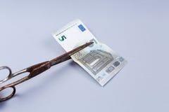 Банкнота евро и ножницы стоковое изображение