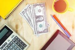 Банкнота доллара США и финансовые калькулятор, ПК таблетки и чашка кофе на деревянном настольном компьютере теплое влияние цвета  Стоковые Изображения RF