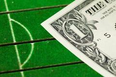 Банкнота положенная на модель футбольного поля Стоковое фото RF