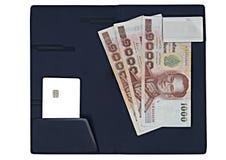 Банкноты денег, кредитная карточка обломока на пусковой площадке выскальзывания знака на изолированном w стоковое изображение
