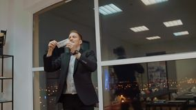 Банкноты денег счастливого бизнесмена целуя и бросать их вверх в офисе акции видеоматериалы