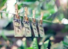 Банкноты доллара США вися на conept отмывания денег веревочки Стоковые Фотографии RF