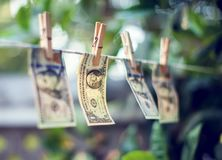 Банкноты доллара США вися на conept отмывания денег веревочки Стоковая Фотография