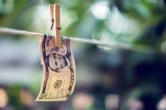 Банкноты доллара США вися на conept отмывания денег веревочки Стоковые Изображения