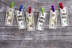 Банкноты долларов вися на веревочке на зажимках для белья Стоковая Фотография RF