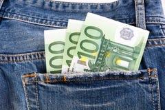 Банкноты 100 евро вставляя из задних джинсов pocket Стоковое фото RF