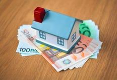 Банкноты евро и символическое свойство приобретения небольшого дома, ипотека стоковая фотография