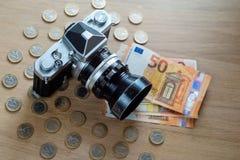 Банкноты евро, монетки и камера на светлой деревянной предпосылке стоковые фотографии rf