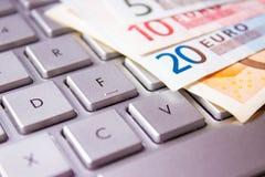 Банкноты евро на клавиатуре компьютера Стоковые Изображения