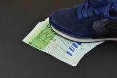 Банкноты евро под ботинками Стоковая Фотография
