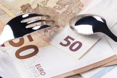 Банкноты 50 и 10 евро в белой плите Поверх их вилка и ложка стоковое изображение rf