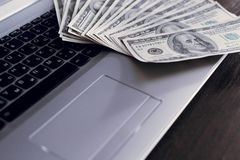 Банкноты над деньгами долларов клавиатуры компьтер-книжки Стоковое Фото