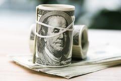 Банкноты доллара в кренах с круглой резинкой на таблице стоковые изображения