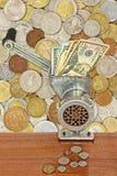 Банкноты доллара в мясорубке и монетки на таблице на серии di Стоковая Фотография