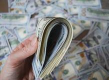 Банкноты доллара наличных денег владением руки женщины Стоковая Фотография