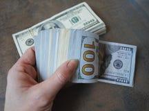 Банкноты доллара наличных денег владением руки женщины Стоковое Изображение RF