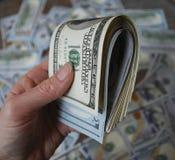 Банкноты доллара наличных денег владением руки женщины Стоковое Фото