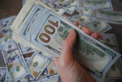 Банкноты доллара наличных денег владением руки женщины Стоковые Изображения RF