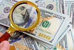 Банкноты доллара под лупой Стоковая Фотография