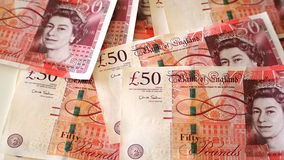 банкноты 50 фунтов разбросали на таблицу, с стороной ферзя Великобритании Стоковая Фотография RF