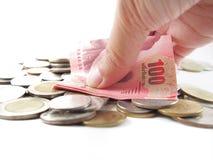 100 банкнот в руке, принимая на кучу тайских денег Стоковое Изображение RF