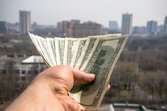100 банкнот доллара в руке человека с городским пейзажем на заднем плане Стоковые Фото