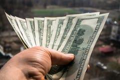 100 банкнот доллара в руке человека с городским пейзажем на заднем плане Стоковое Изображение