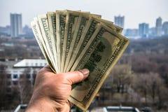 100 банкнот доллара в руке человека с городским пейзажем на заднем плане Стоковая Фотография