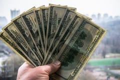 100 банкнот доллара в руке человека с городским пейзажем на заднем плане Стоковая Фотография RF