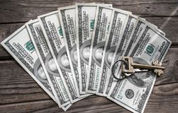 100 банкнот доллара закрывают вверх с плоским ключом на деревянной предпосылке Стоковые Изображения RF