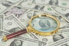 100 банкнот доллара под лупой Стоковое Изображение