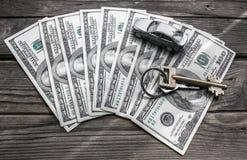 100 банкнот доллара с домашним ключом и автомобиль игрушки на деревянной предпосылке Стоковая Фотография RF