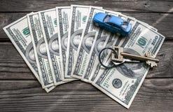 100 банкнот доллара с домашним ключом и автомобиль игрушки на деревянной предпосылке Стоковые Фотографии RF
