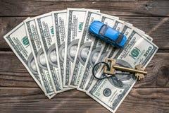 100 банкнот доллара с домашним ключом и автомобиль игрушки на деревянной предпосылке Стоковые Изображения RF