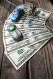 100 банкнот доллара с домашним ключом и 2 автомобиля игрушки на деревянной предпосылке Стоковые Изображения RF