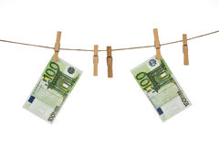 100 банкнот евро вися на веревке для белья на белой предпосылке Стоковая Фотография