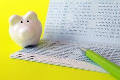 Банковская книжка на предъявителя, копилка и ручка сберегательного счета на желтой предпосылке Стоковая Фотография RF