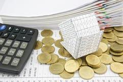 Банкротство дома на золотых монетках и калькуляторе кучи Стоковое Фото