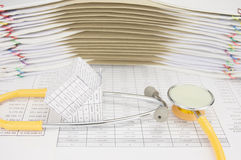 Банкротство дома с желтым стетоскопом на учете финансов Стоковое Изображение RF