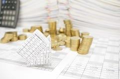 Банкротство дома с золотыми монетками понижается к земле Стоковая Фотография